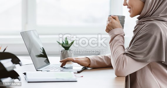 istock Unrecognizable muslim woman in hijab drinking coffee and typing on laptop 1209185790