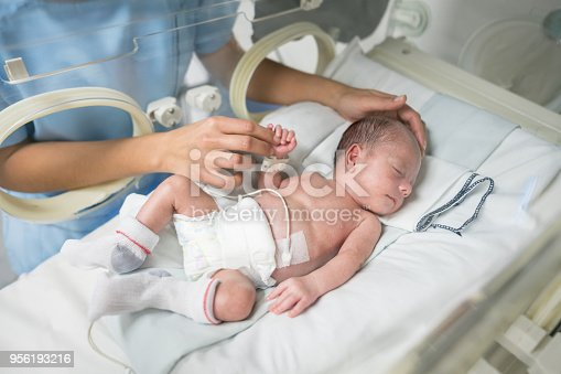 Unrecognizable nurse caressing a newborn baby in an incubator while he sleeps very peacefully