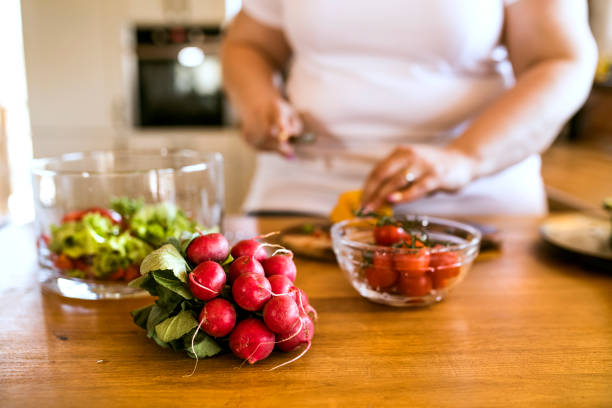 Unrecognizable overweight woman at home preparing a delicious healthy vegetable salad in her kitchen. stock photo