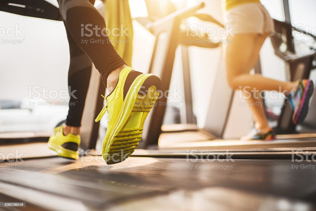 Unrecognizable people running on treadmills in a gym. stock photo