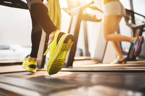 Unrecognizable people running on treadmills in a gym. Two unrecognizable people exercising on treadmill in a health club. treadmill stock pictures, royalty-free photos & images