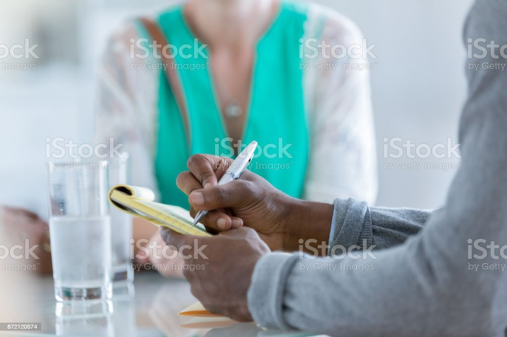 Unrecognizable people sit at a table and brainstorm stock photo