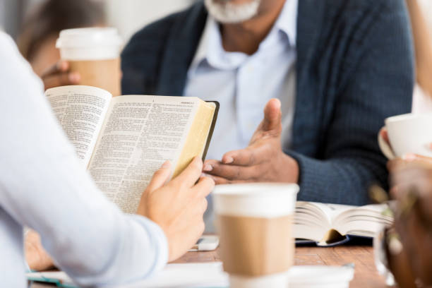 Unrecognizable people studying the Bible Unrecognizable people meet up at a coffee shop to study the Bible together. A woman holds the Bible in the foreground. clergy stock pictures, royalty-free photos & images