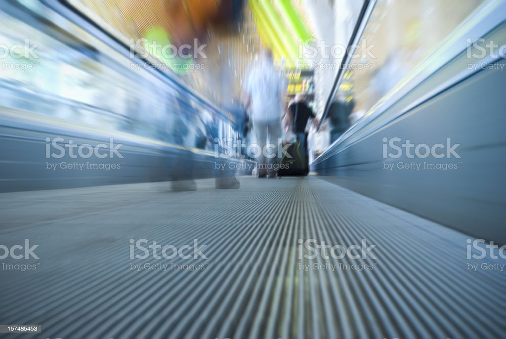 Unrecognizable people travelling, airport escalator, motion blur stock photo