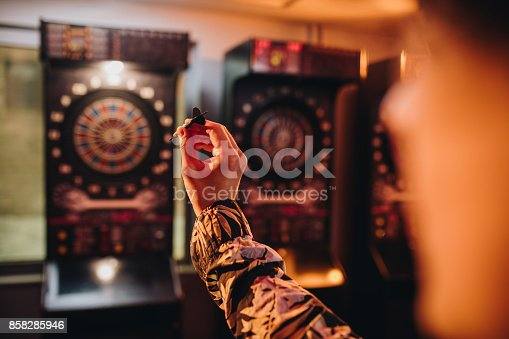 Hand of a man holding dart and aiming while playing darts in entertainment club.
