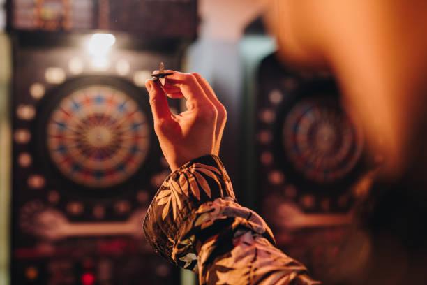 Unrecognizable person aiming at dartboard in a pub. stock photo