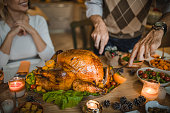 Unrecognizable man carving roasted Thanksgiving turkey during dinner at dining table.