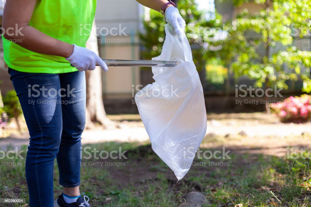 A photo of an unrecognizable person while cleaning a public park in...