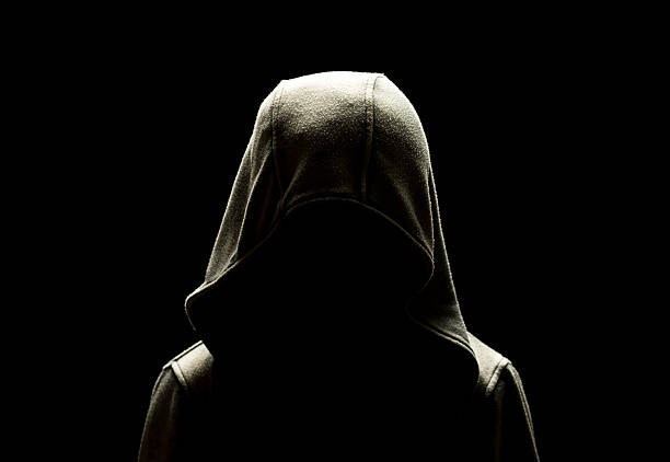 unrecognizable person dressed in hooded jacket in the dark stock photo