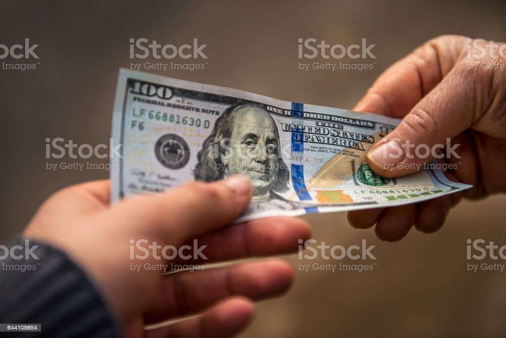 Unrecognizable person giving other person USA Dollar bill stock photo