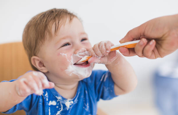 Unrecognizable Person Giving Yogurt With a Spoon To a Baby Boy stock photo
