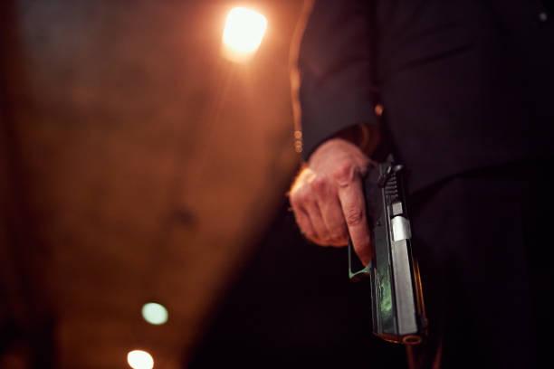 Unrecognizable person holding a handgun at night stock photo
