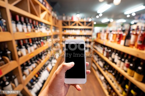 Unrecognizable person holding a smartphone at a wine cellar - Copy space