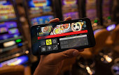 Unrecognizable person holding a smartphone with a sports betting application on screen