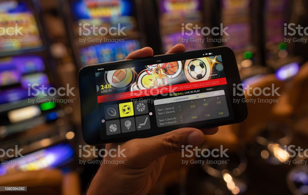 Unrecognizable person holding a smartphone with a sports betting application on screen stock photo