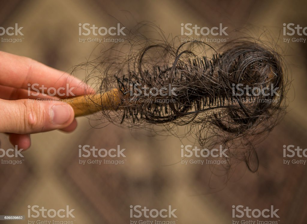 Unrecognizable person holding hairbrush with spilled hairs stock photo