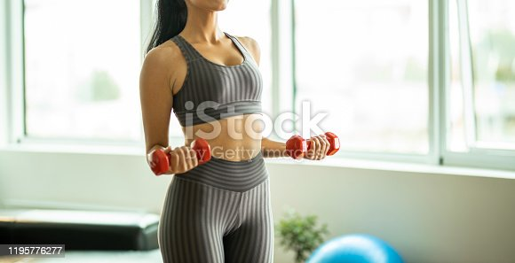 1035512048istockphoto Unrecognizable person holding weights 1195776277