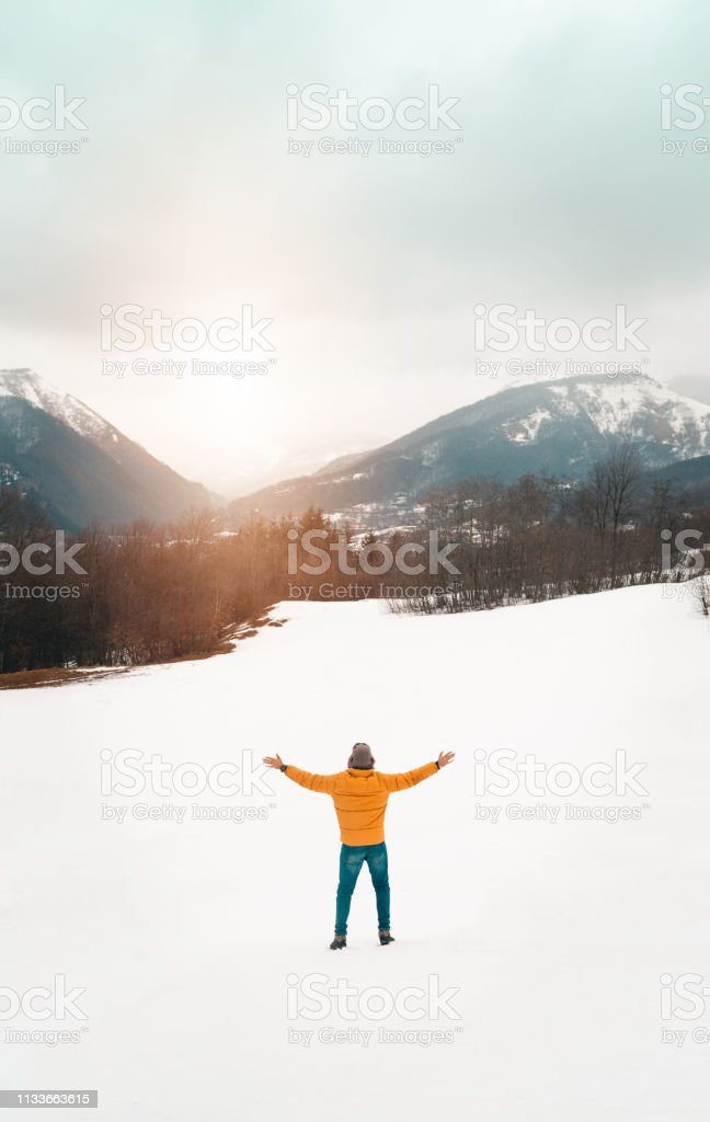 Unrecognizable person looking at snowy mountains with open arms