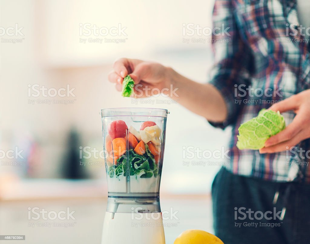 Unrecognizable person making smoothie. stock photo