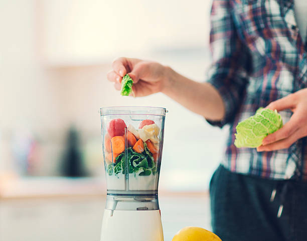 Unrecognizable person making smoothie. Closeup of unrecognizable person hand adding kale to smoothie. Filling blender with fruits and vegetables for fresh healthy smoothie or juice. She already added apple, kale, cherry tomatoes, kiwi, carrot, blender stock pictures, royalty-free photos & images