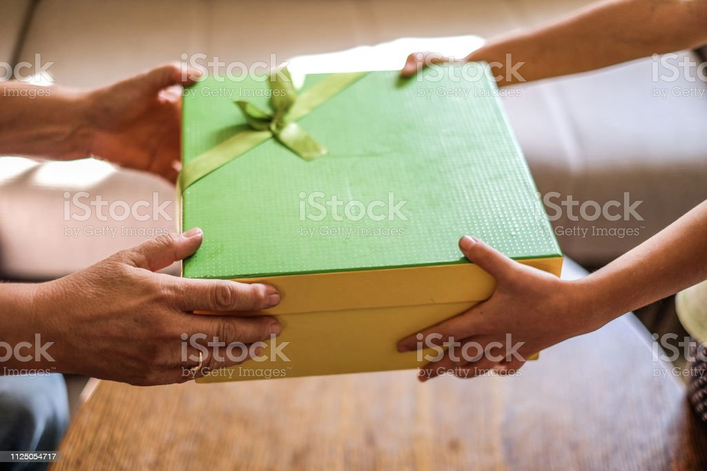 a birthday gift box and human hands holding it