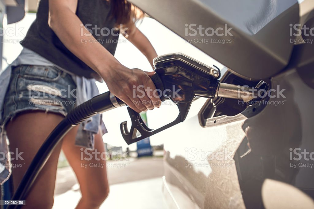 Unrecognizable person refueling gas tank at fuel pump. stock photo