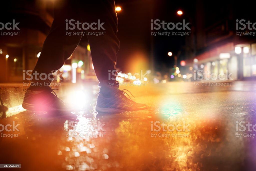 Unrecognizable person stepping into a puddle during rainy evening