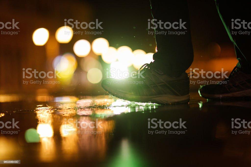 Nie rozpoznawalna osoba wchodząca w kałużę podczas deszczowego wieczoru - Zbiór zdjęć royalty-free (But sportowy)