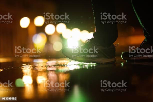 Nie Rozpoznawalna Osoba Wchodząca W Kałużę Podczas Deszczowego Wieczoru - zdjęcia stockowe i więcej obrazów But sportowy