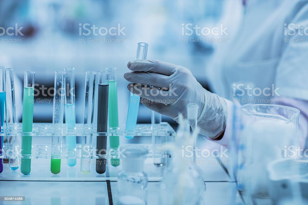 Unrecognizable person taking a test tube for an experiment. stock photo