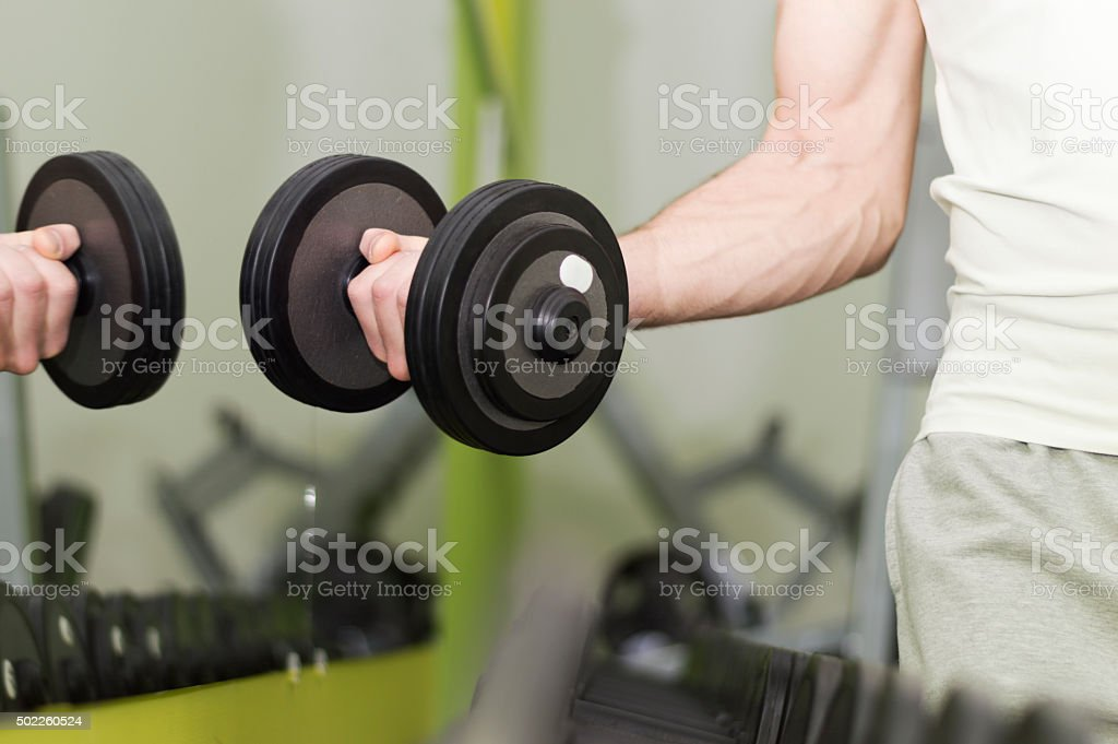 Unrecognizable man taking dumbbell from a rack.