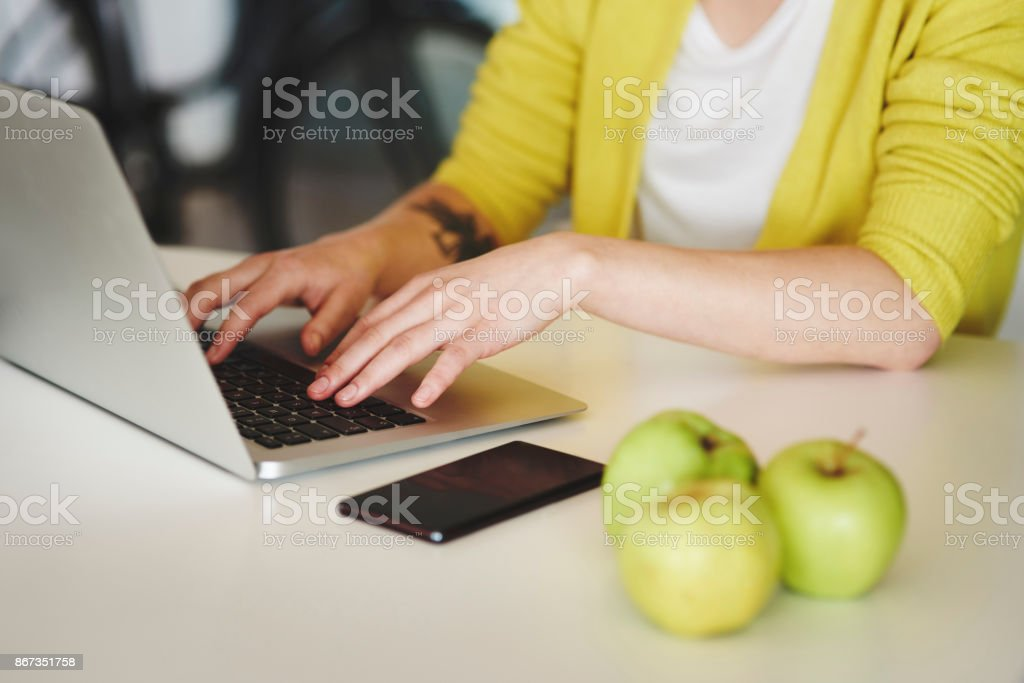 Unrecognizable person typing on laptop keyboard stock photo