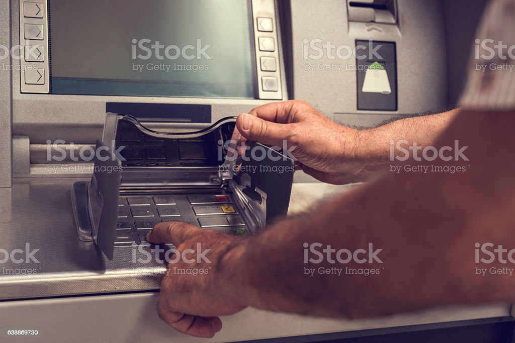 Unrecognizable person typing PIN on a cash machine. stock photo