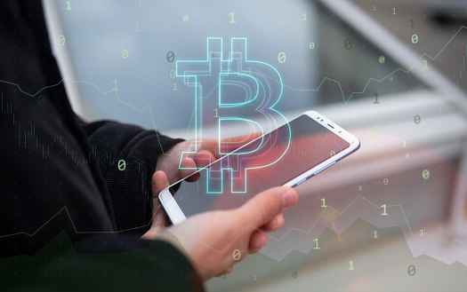 Unrecognizable person using his smart phone and trading Bitcoin. Bitcoin / Cryptocurrency concept.