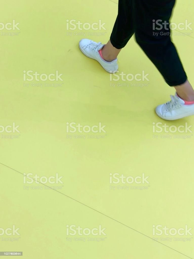 Unrecognizable person walking on yellow floor
