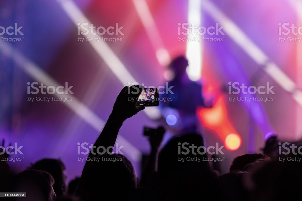Unrecognizable fan taking picture of stage performers at music...