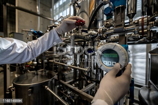 Unrecognizable person working at a process lab opening a valve while looking at screen - Pharmaceutical industry