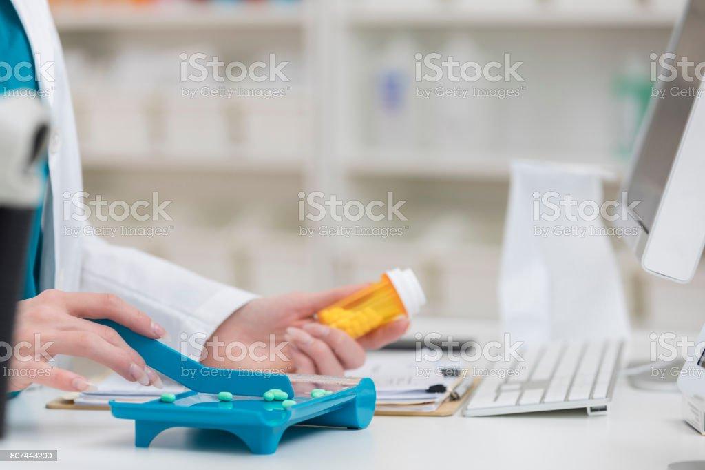 Técnico de farmacia irreconocible sostiene la botella de la prescripción y cuenta tabletas - foto de stock