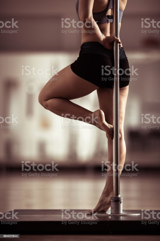 Unrecognizable pole dancer's body leaning on a pole. stock photo