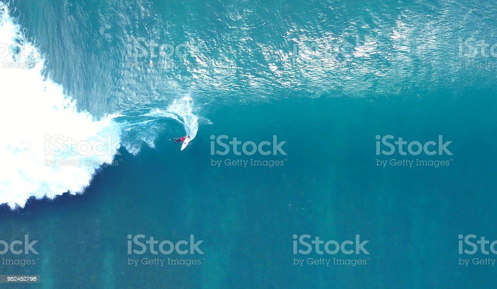 TOP DOWN: Unrecognizable pro surfer riding a stunning blue ocean wave in the sun stock photo