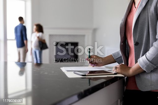Female real estate agent finishes up paperwork as a couple discuss the purchase of a new home in  the background.