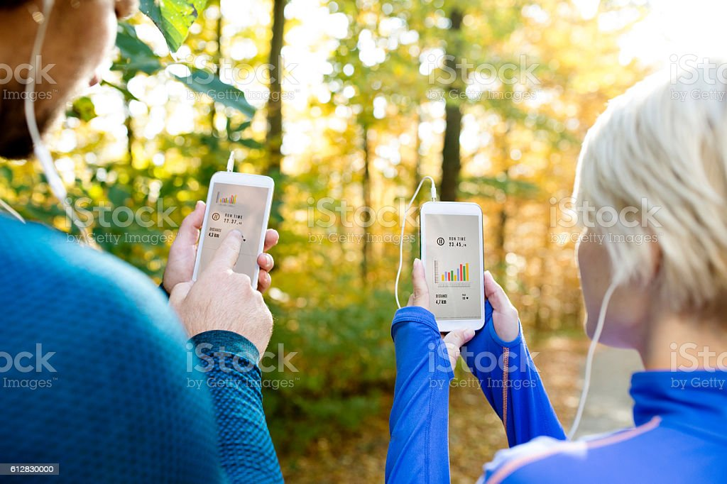 Unrecognizable running couple with smart phones and earphones stock photo
