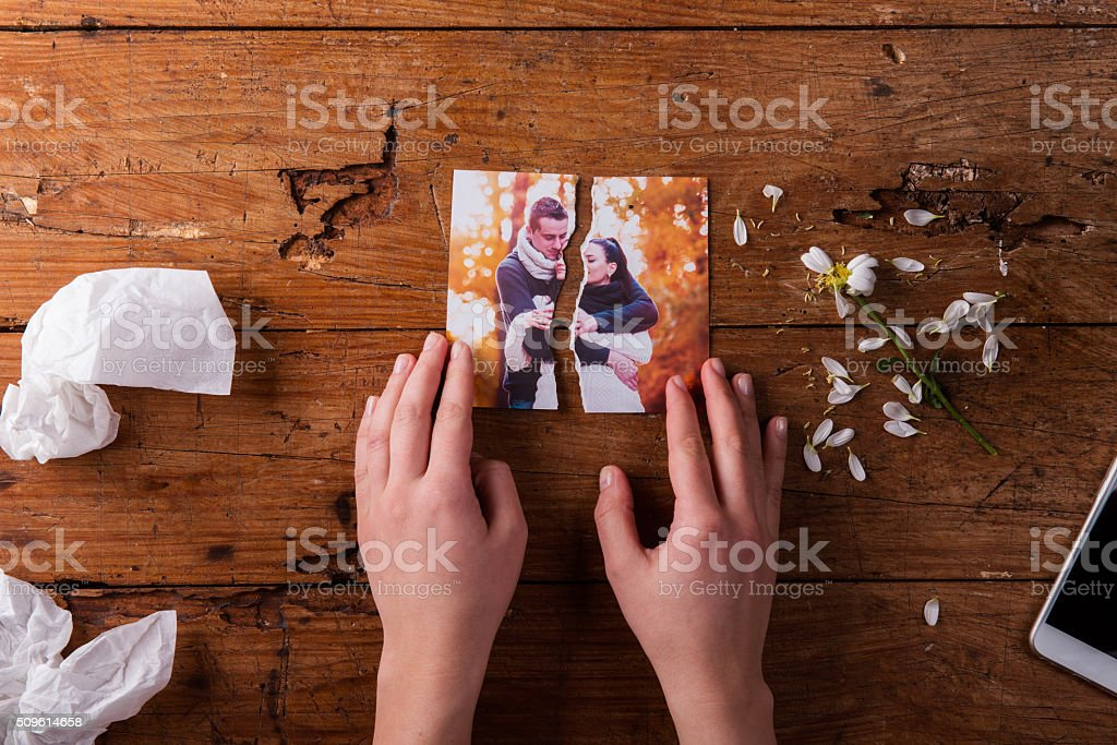 Unrecognizable sad woman holding torn picture of couple in love. stock photo