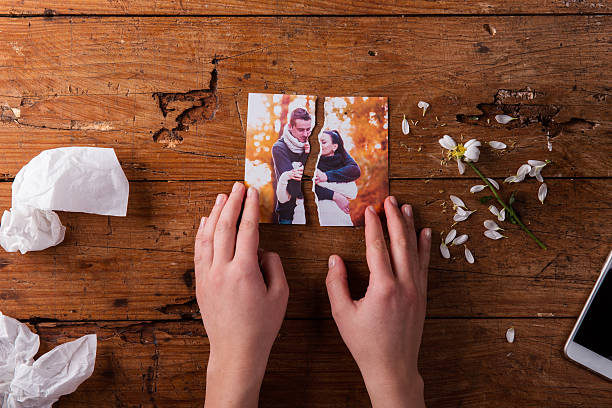 unrecognizable sad woman holding torn picture of couple in love. - separation stock photos and pictures