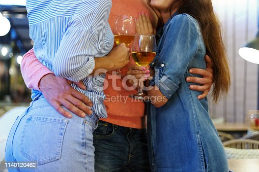 Unrecognizable seducer hugging two girls at once at party. Women holding glasses of wine