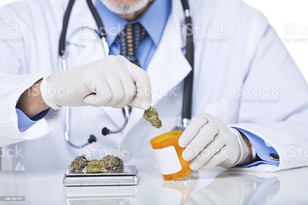 Unrecognizable senior doctor dispensing cannabis from scale to bottle stock photo