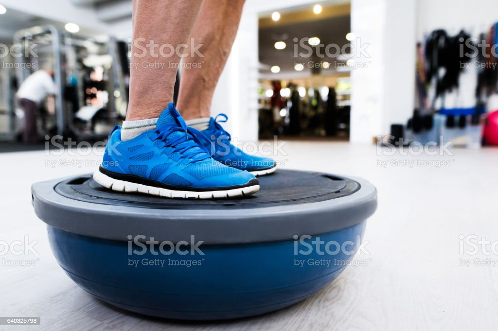 Unrecognizable senior man in gym standing on bosu balance ball stock photo