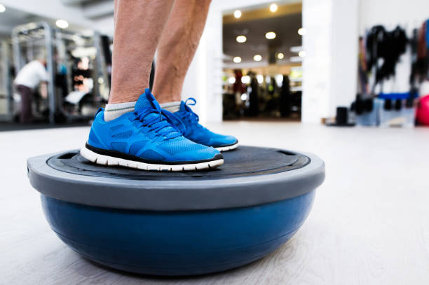 unrecognizable senior man in gym standing on bosu balance ball - balance stock pictures, royalty-free photos & images