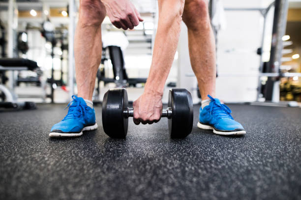 unrecognizable senior man in gym working out with weights - old man feet stock photos and pictures