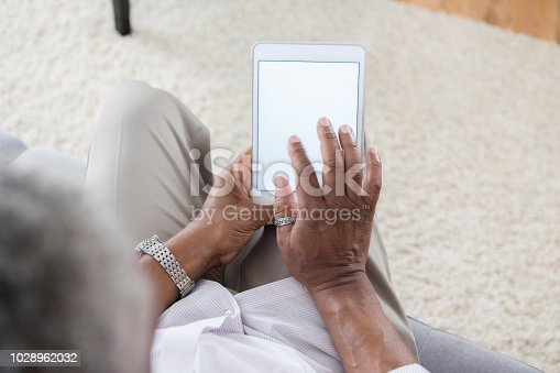 Senior African American man uses digital tablet at home. The device screen is blank.